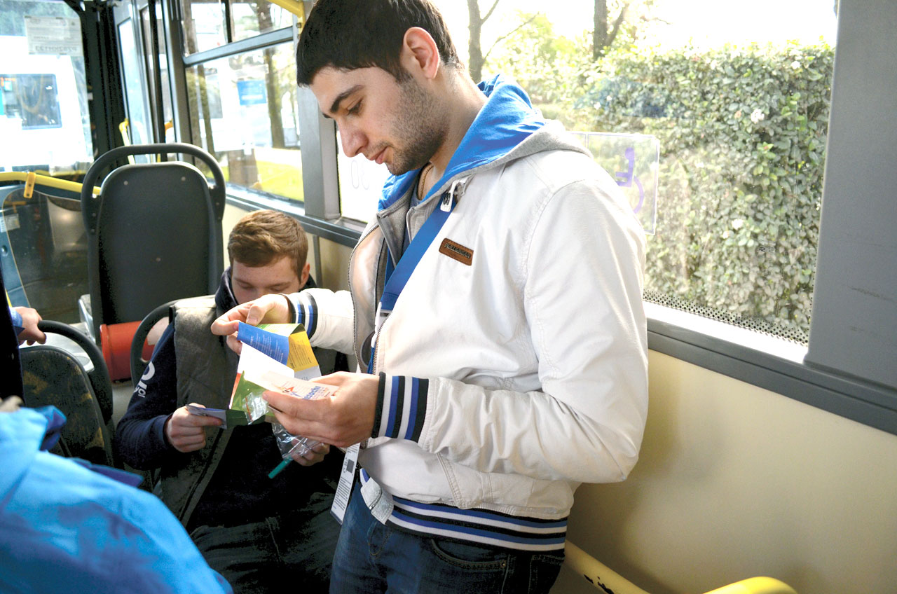 Two young Russian men read the gospel presentation that was attached to the Engage Sochi pins as they ride the bus in Sochi, Russia. Members of the Singing Men of Oklahoma and their companions each had 50 pins to trade or share with those they met on their recent trip to the XXII Winter Olympics (Photo: Bob Nigh)