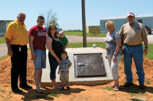 Cecilia Breedlove, second from right, and her grandchildren, Chris and Sarah Geddes and their sons, Zechariah and Christopher (Standing) are grateful for their new mobile home in Steelman Estates (In background at right) provided by the BGCO, represented by Porter, left, and Oil Patch Chaplaincy Consultant Tom Beddow, right. The BGCO also installed the new in-ground concrete storm shelter near their home. (Photo: Bob Nigh)