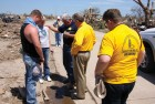 From left, two victims of the May 20, 2013 Moore tornado are prayed over by Baptist General Convention of Oklahoma (BGCO) Disaster Relief Director Sam Porter, BGCO Executive Director-Treasurer Anthony L. Jordan and another BGCO official. The BGCO cleared the home sites at no charge of more than 1,200 of the 4,035 houses that were reported destroyed or damaged by the tornado (Photo: Brian Hobbs)