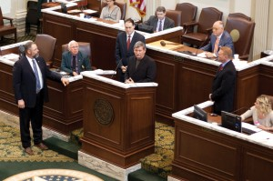 CAPITOL HONOR: Awe Star Ministries President Walker Moore, at podium, makes comments after being honored by the Oklahoma House of Representatives April 17. The effort was led by State Rep. Wade Rousselot, standing left, in recognition of Moore's carrying a cross to the top of Mt. Kilimanjaro last year.