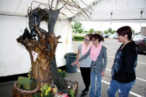 "From right, Tara Fanning, Alexis Fanning and Hayden Gardiner, look at the ""Rising from the Rubble"" sculpture made by a local artist. The sculpture, which was featured in the film, was made from pieces of rubble after the storm and family photos from those affected by the tornado."