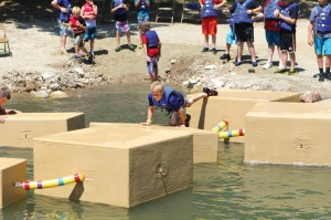 Children challenge themselves at the lakefront to jump on boxes without falling in.