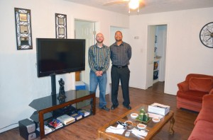 Assistant Director Jeff Elbert, left, and Senior Pastor Rick Gettens  display the result of months of a labor of love by members of Lawton, Mind of Christ Multiethnic to repair one of the units of the Living Life: Housing with a Purpose program in the living room and kitchen of the first residence to house a participant in the program.