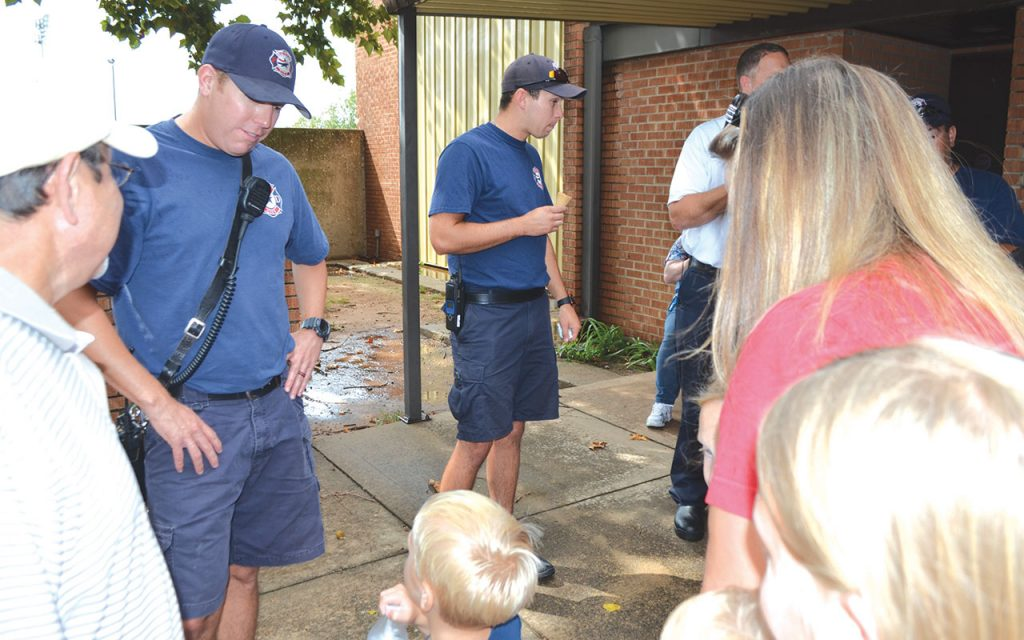 Midwest City firefighters visit with a young admirer and his family at the Aug. 25 ice cream social.