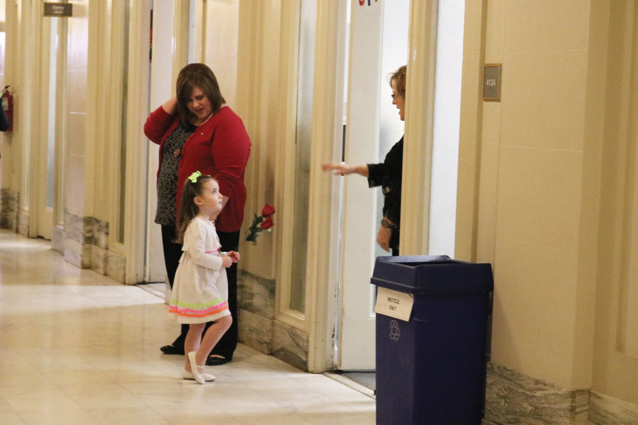 A mother and her child distribute roses to House and Senate members
