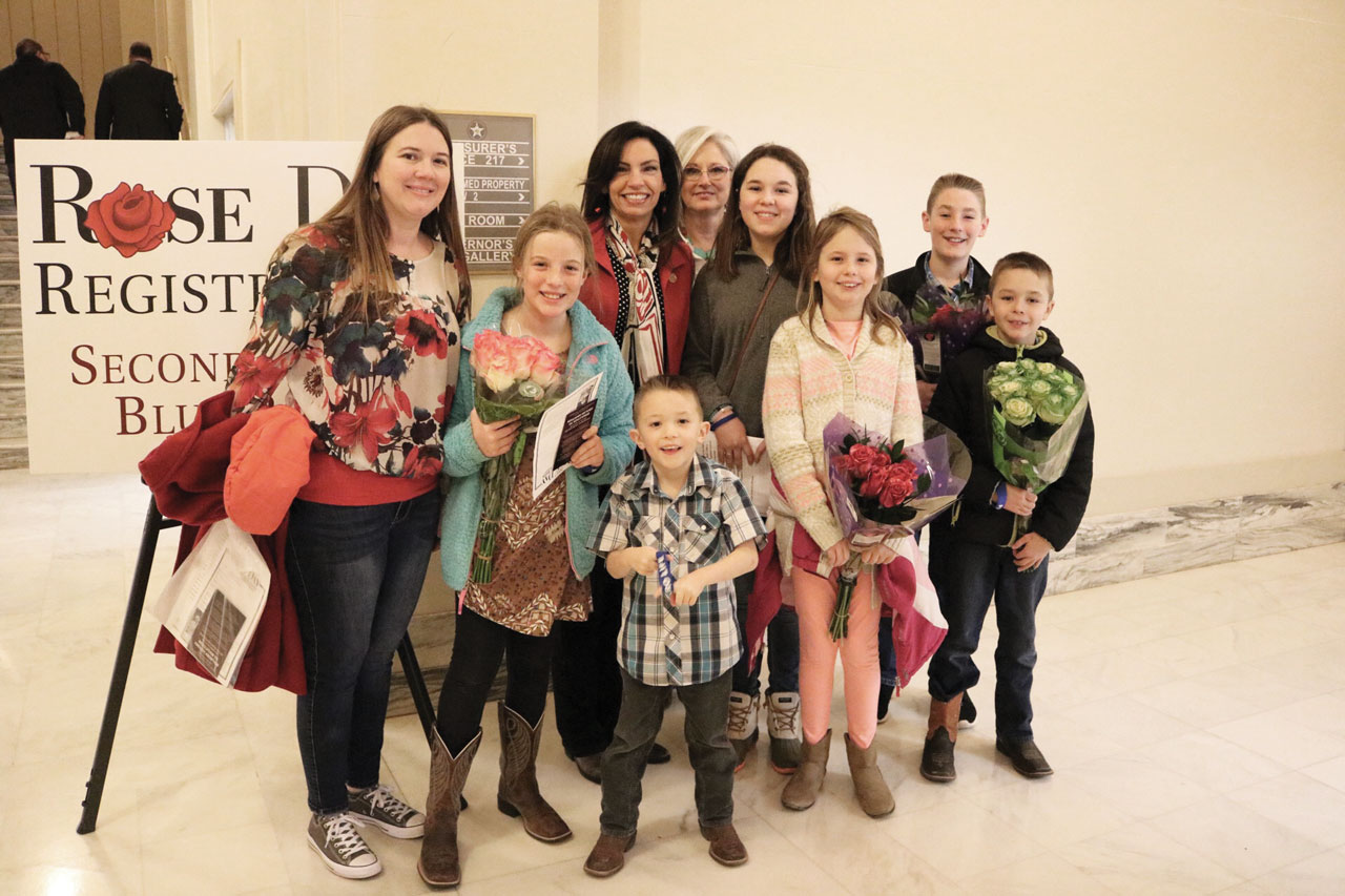 Mothers pose with their children and Rose Day Committee member Lisa Billy outside of Rose Day registration, roses in hand